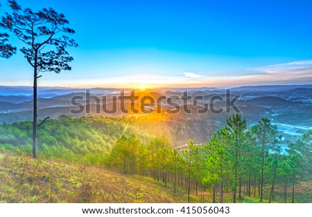 Early on a sunny plateau Da lat with rays radiating from horizon, beneath  rolling mountains in mist covered pine forest warm welcome new day in Vietnam - stock photo