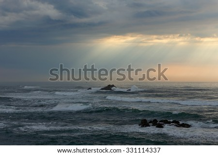 Early spring cloudy seascape before storm seeing natural sunbeams at sunset. Northern portuguese coast. - stock photo