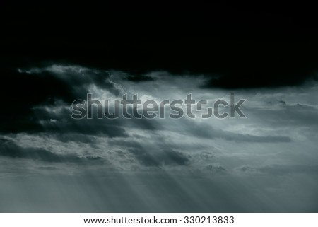 Early spring cloudy sky with natural sunbeams. Black and white toned blue. - stock photo