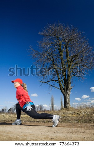 Early spring exercising on dirt country road. Woman stretching outdoors after running. Happy female runner on outdoors exercising workout in nature. - stock photo