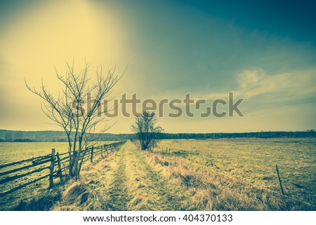 Early spring landscape with rural meadow and farm, pasture with dry grass, vintage photo - stock photo