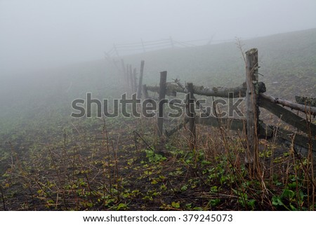 Early spring landscape. Wooden fence on the agricultural meadow near path on the hillside. Dense fog. - stock photo
