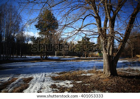 early spring snow melts in the park landscape - stock photo