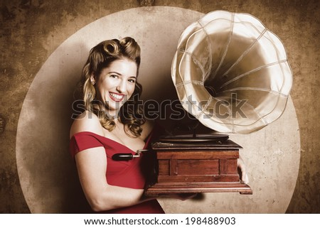 Early 21st century vintage pin-up girl adjusting stylus when listening to recorded sound waves through phonograph or record player.  Groovy honky tonks or juke joints entertainer - stock photo