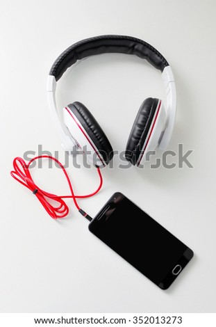 Earphones and smart phone lie on a white table. A black background on phone display. - stock photo