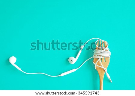 Earphones on wooden fork. Concept of Music. - stock photo