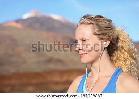 Earphones - woman runner listening to music in earbuds from smartphone. Female athlete portrait after running in beautiful nature. Healthy lifestyle concept with beautiful young blonde fitness model. - stock photo