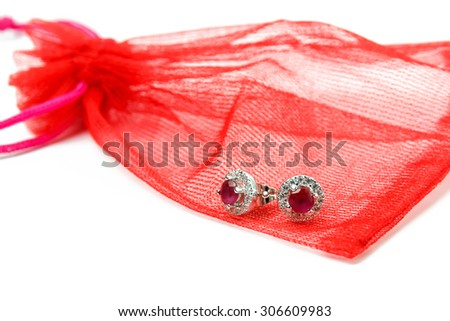 earring and red jewelry bag on white background. - stock photo