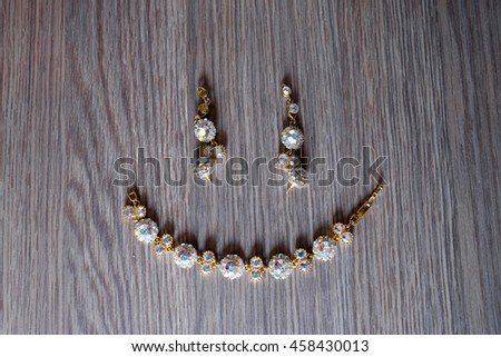 Earrings and bracelet lay in the form of emoticon on wood texture - stock photo
