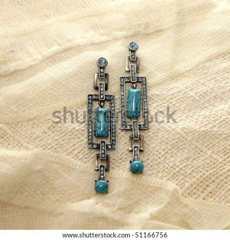 earrings with turquoise on a background of white linen and lace - stock photo