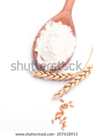 Ears of wheat and flour in the wooden spoon, isolated on white background - stock photo