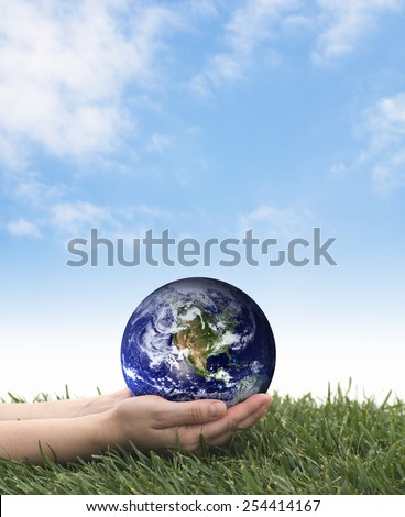 Earth Day. Hands holding earth over grass on a blue sky. The planet earth image provided by NASA. - stock photo