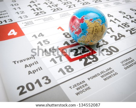 Earth day marked on the calendar with a globe as a symbol. - stock photo