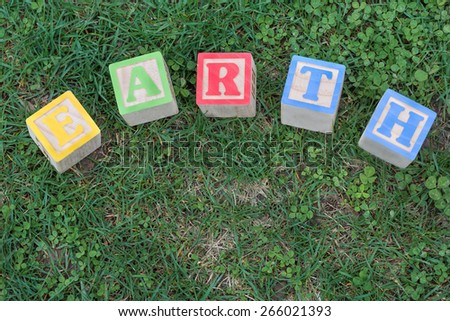 Earth day wooden blocks against natural grass and clover.  Colorful wooden blocks laid in a curve to spell Earth on ground.  - stock photo