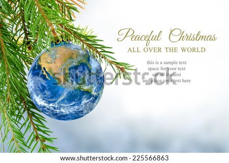earth globe as Christmas ball hanging in fir branch, message: peaceful Christmas all over the world, symbol, metaphor, copy space, bright snowy background. Elements of this image furnished by NASA. - stock photo