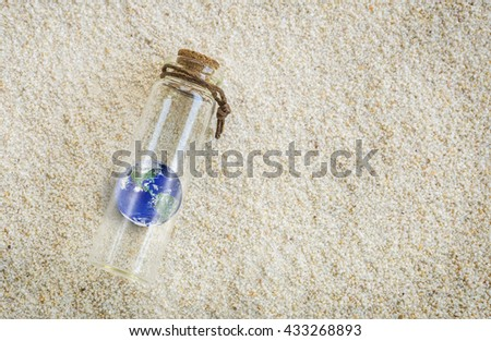 Earth in a Bottle on the sand, planet earth inside a glass jar on the sand, safe our earth concept, message to the world concept, Elements of this image furnished by NASA - stock photo