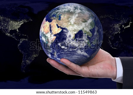 earth in a hand on background night city - stock photo