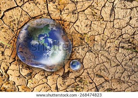 Earth in water drop reflection on dry soil background ,no plant on earth concept,  Elements of this image furnished by NASA - stock photo