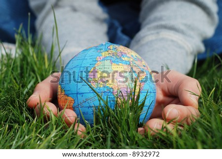 earth is being held by a little girl's hands - stock photo