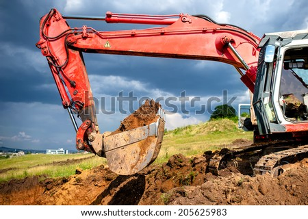 earth mover, industrial digger and excavator working in sandpit on construction site - stock photo
