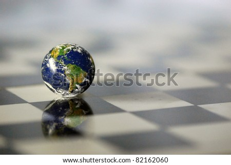 Earth on a chessboard - stock photo