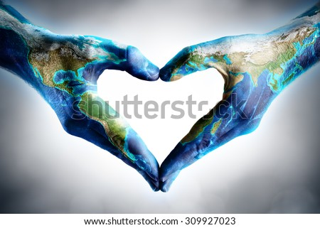earth's day celebration - hands shaped heart with world map - elements of this image furnished by NASA  - stock photo