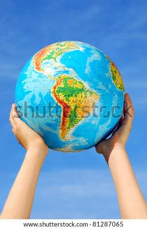 earth`s globe holding in hands against blue sky - stock photo