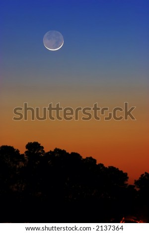 Earthshine (reflected sunlight from Earth lights the dark portion of a Crescent moon ) - stock photo