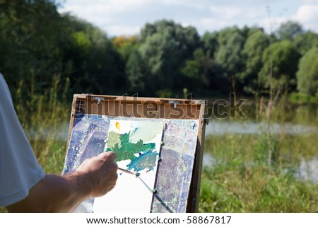 Easel artist in nature. Draw landscape from nature. - stock photo