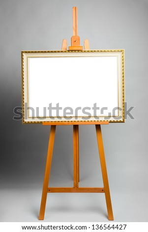 easel with painting frame on grey background - stock photo