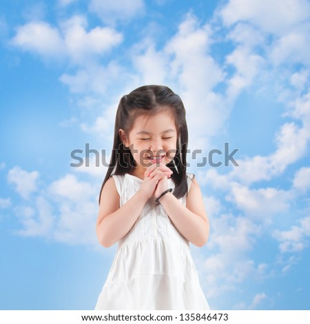 East Asian girl making a wish with smiling, blue sky as background - stock photo