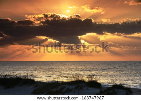 East Coast landscape of sun rising over the Atlantic Ocean on Cape Hatteras National Seashore in Frisco, North Carolina on the outer banks.   - stock photo