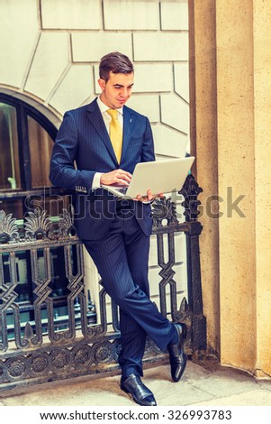 East European Businessman working in New York. Dressing in striped blue suit, yellow tie, leather shoes, a young guy standing on balcony outside office, reading, working on laptop computer.  - stock photo