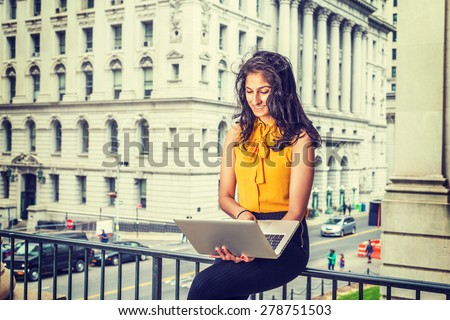 East Indian American Business Woman in New York. Wearing sleeveless orange shirt, a beautiful college student sitting by office building on street, looking at laptop computer, reading, working.  - stock photo