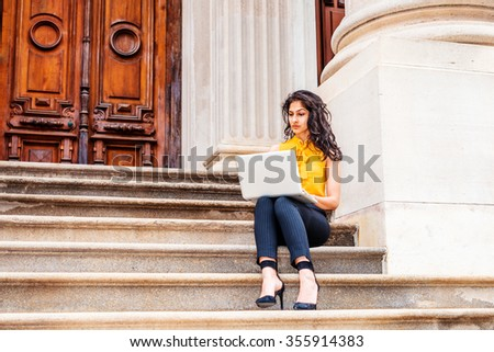 East Indian American college student studying in New York, wearing sleeveless orange shirt, striped pants, high heels, sitting on stairs outside office building on campus, working on laptop computer. - stock photo