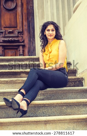East Indian American College Student. Wearing sleeveless orange shirt, striped pants, high heels, a beautiful business woman with long curly hair sitting on stairs outside office, taking a break. - stock photo