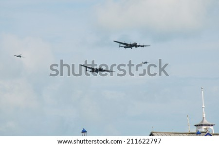 EASTBOURNE, ENGLAND - AUGUST 14, 2014: Lancaster bomber PA474 of the Battle of Britain Memorial is followed by Canadian Lancaster KB726 and Spitfire and Hurricane fighters at the Airbourne airshow. - stock photo