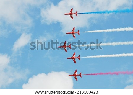 EASTBOURNE, ENGLAND - AUGUST 14, 2014: RAF aerobatic team The Red Arrows perform at the annual Airbourne airshow. Formed in 1965, the team are in their 50th display season. - stock photo