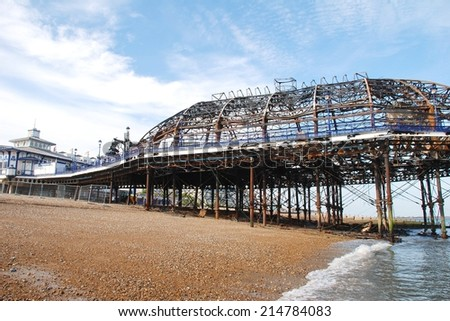 EASTBOURNE, ENGLAND - JULY 31, 2014: The Victorian pier which was badly damaged by fire on July 30, 2014. Designed by Eugenius Birch, the landmark was first opened in 1870. - stock photo