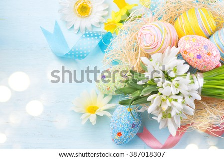Easter background. Beautiful colorful eggs with decorations and spring flowers on the wooden table, pastel colors, border design - stock photo