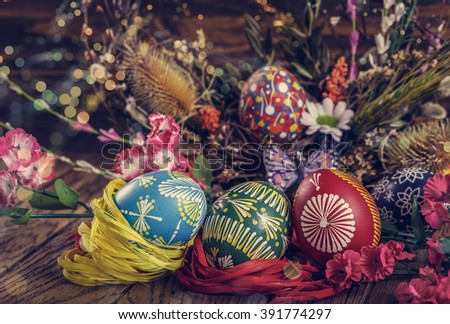 Easter background. colored Easter eggs and composition of dried flowers and plants. on wooden background. easter theme. happy easter. instagram toning effect. light effect. bokeh - stock photo
