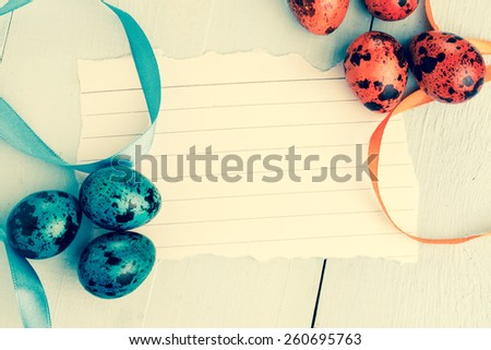 Easter background. Colorful easter eggs on wooden background with easter greeting note paper. - stock photo