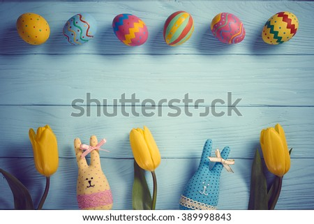 Easter background, eggs, rabbits and yellow tulips. Hand painted decorated eggs, happy bunny handmade and spring flowers, blue wood, copy space. Still life, top view. Unusual creative greeting card  - stock photo
