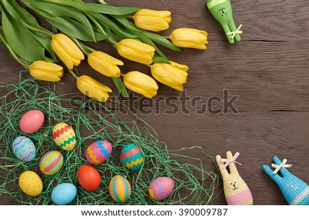 Easter background, eggs, rabbits and yellow tulips. Hand painted decorated eggs on straw, happy bunny handmade and spring flowers, wood, copy space.Still life, top view.Unusual creative greeting card  - stock photo