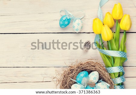 Easter background with blue and white eggs in nest and yellow tulips. Top view with copy space. Vintage toned  - stock photo