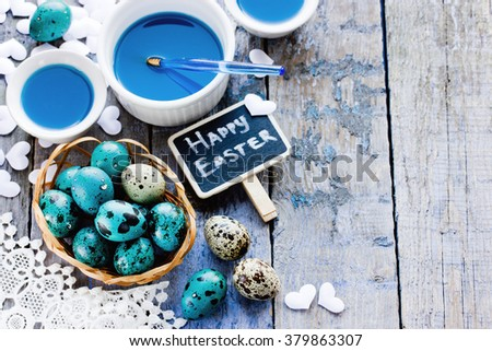 Easter background with colored eggs white hearts and blue paint on wooden table preparation for the spring holiday - stock photo