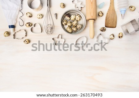 Easter bake tools with quail eggs and biscuit cutter on white wooden background, top view, place for text - stock photo