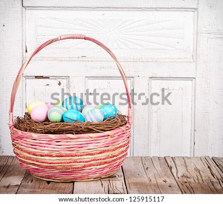 Easter basket with Easter eggs on a wooden plank with antique cracked panel for background - stock photo