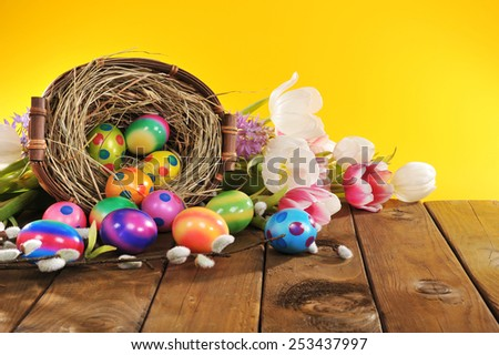 Easter basket with many colored hen�s eggs, tulip and hyacinth on old wooden board - stock photo
