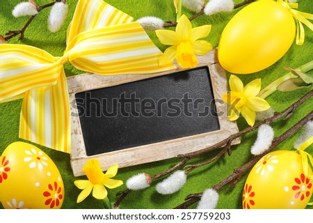 Easter blackboard with copy space, yellow easter eggs, narcissus and pussy willow on tablecloth  - stock photo